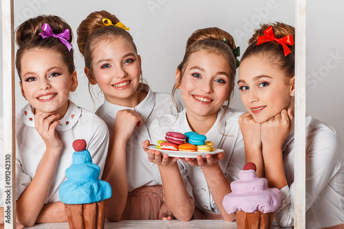 Foto op Aluminium Macarons Beautiful teenage model girls in pink tutu or tullу skirts with macaroons, fancy cakes and sweets in studio on white background