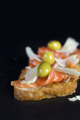 A fresh salmon sandwich with cheese on black background.