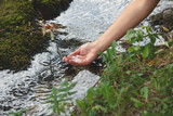 woman hand with water from a pure mountain stream - 191249509
