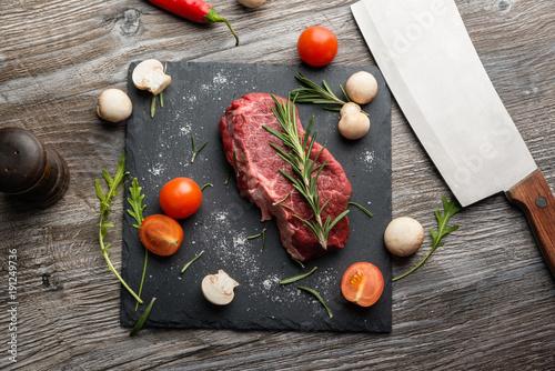Foto op Aluminium Steakhouse Cooking raw beefsteak with herbes