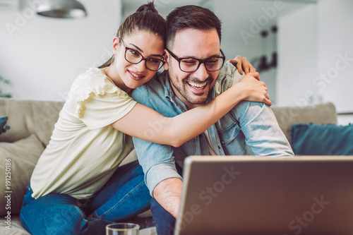 Happy couple with laptop spending time together at home