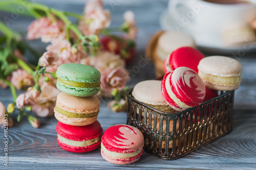 Macarons on rustic wood table, French candy meringue-based made with egg white, icing sugar, granulated sugar, almond powder or ground almond and food coloring - 191253575