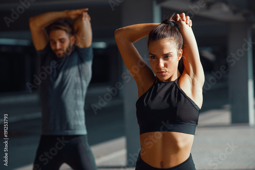Plexiglas Fitness Young sports couple exercising in the urban environment