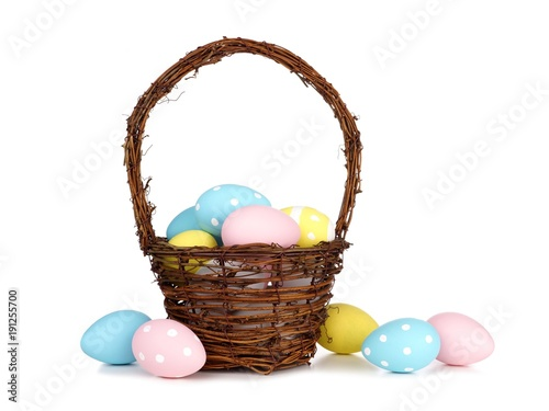 Easter basket filled with colorful hand painted blue, pink and yellow Easter Eggs over a white background