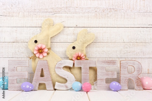 Easter spelled in rustic wooden letters with surrounding eggs and bunnies. Side view with a white wood background.