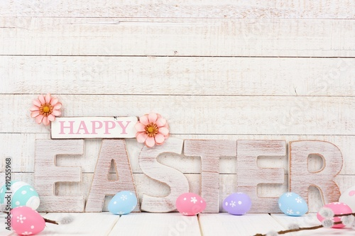 Happy Easter spelled in rustic wooden letters with surrounding Easter eggs. Side view with a white wood background.