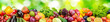 Panorama of fresh vegetables and fruits on blurred background of green leaves.