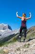 young female woman hiker with active wear flexing arms in a strong pose in the mountains