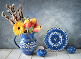 Spring flowers in blue ceramic pitcher with matching plate and  Easter eggs on gray - 191279501