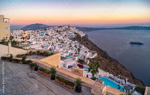 Foto op Canvas Santorini Abendlicher Blick über die weißen Häuser von Santorin, ein berühmtes Postkartenmotiv mit einem Kreuzfahrtschiff im Hintergrund