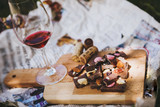 Glass with red wine and pieces of chocolate with nuts and raisins - 191285992