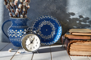 Alarm clock, ceramic plate and a pitcher with pussy-willow and old books