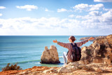 Girl traveler with a backpack sits on the rocks on the ocean, admiring the incredible scenery. Portugal, the Algarve, a popular destination for travel in Europe