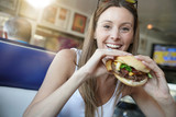 Portrait of cheerful girl eating hamburger in fast food restaurant - 191294182