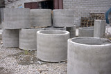 Concrete ring wells with different diameters and gray lie in the street . - 191298302