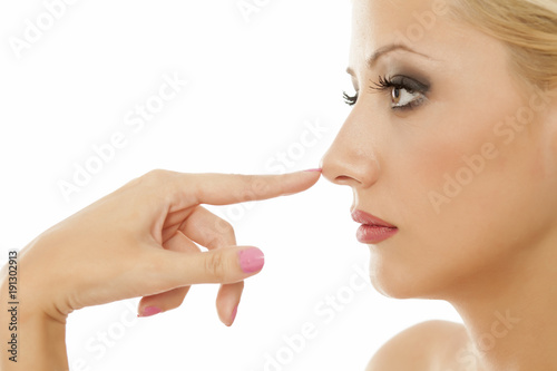 Young blonde touches her nose on white background