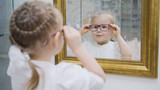 Little girl tries new glasses near mirror - shopping in ophthalmology clinic - 191322152