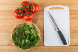 Tomatoes, wicker basket with greens, cutting board and kitchen knife - 191323982