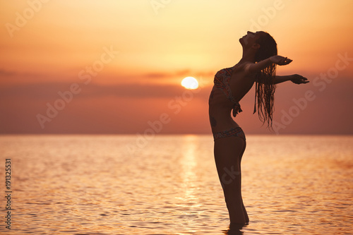 silhouette-of-a-beautiful-sexual-girl-against-the-sea-and-sunset-happy-woman-stands-in-the-sea-with-wide-opened-hands-and-enjoys-a-summer-vacation