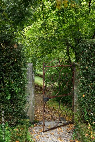 Fotobehang Weg in bos grille ouvrant sur un jardin