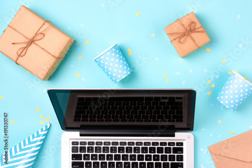 Gift box, birthday party things and laptop on a blue background