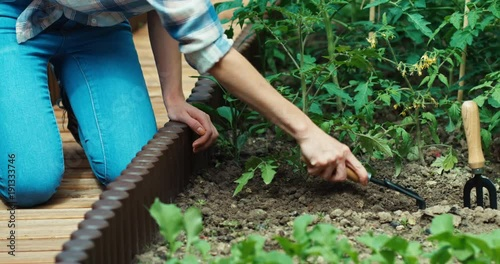 Woman loosening soil in kitchen garden