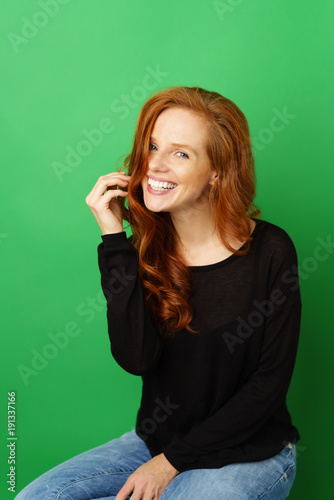 Smiling woman in casual clothes with long red hair