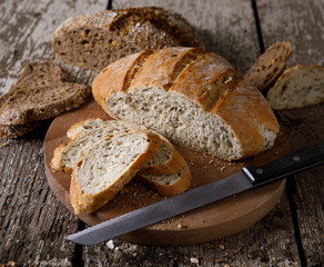 Fresh bread slice and cutting knife on rustic table.