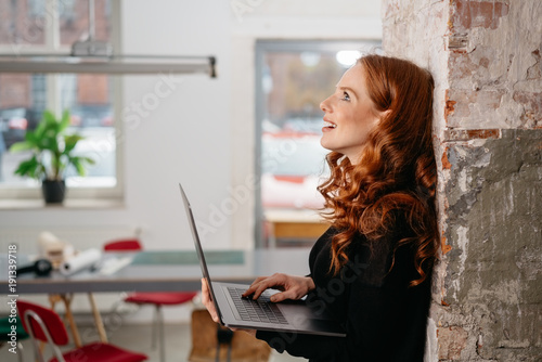 Foto Murales Young woman thinking as she uses her laptop