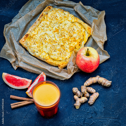 Foto Murales Still life with an apple, slices of grapefruit, ginger root, coconut tea and apple pie with cinnamon. Modern style on a concrete background. Vegetarian cuisine, healthy food