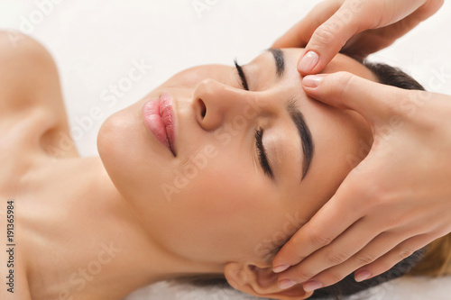 Woman getting professional facial massage at beauty salon
