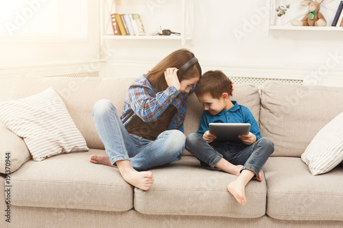 Two kids listening music on couch at home
