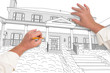 Male Hands Sketching with Pencil the Outline of a Beautiful House on White.