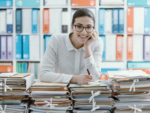 Foto Murales Smiling office clerk and piles of paperwork