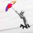 Funny woman jumping with umbrella