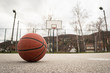 Used orange basketball with basket in background. Basketball street court