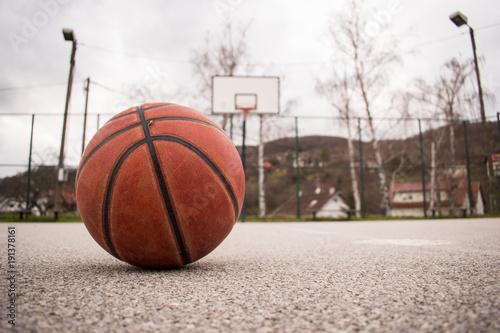 Fotobehang Basketbal Used orange basketball with basket in background. Basketball street court