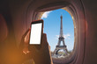 Woman sitting by aircraft window and using a digital mobile during the flight. Eiffel tower as seen through window of an aircraft.