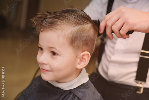 cute baby boy in a barber's chair in barbershop. Children's haircut.