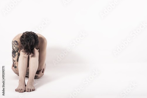 Tattooed naked woman with depression sitting in hunched pose on white background