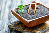 Poppy seeds in a wooden bowl. - 191397329