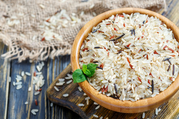 Red, white, brown and wild rice in a wooden bowl closeup.