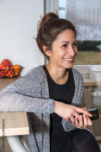 Junge Frau mit Duttfrisur hält Smartphone und sitzt lächelnd auf Stuhl in Küche