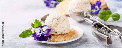 Vanilla ice cream scoop with edible flowers pansy. Summer food concept with copy space.
