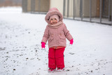 Adorable girl in winter jacket running on the snow - 191468503