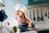 adorable child in chef hat sitting in kitchen and smiling at camera - 191473177