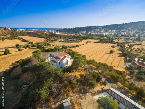 Poster Cyprus Aerial bird eye view of Saint George chapel (parekklisi Agiou Georgiou) in Germasogia municipality, Limassol, Cyprus on a hill by the sea inside hay fields at summer. A christian greek orthodox church