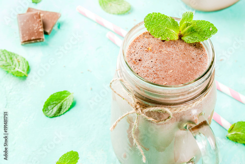 Foto op Aluminium Milkshake Chocolate smoothie or milkshake with mint and straw, in mason jar on light blue background, copy space