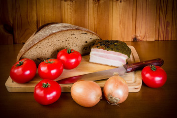 Ham, tomatoes, onion and bread on wooden cutting board on wooden table. Selective focus