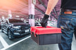 The abstract image of the back of technician hold a toolbox and blurred garage is backdrop. the concept of automotive, repairing, mechanical, vehicle and technology.